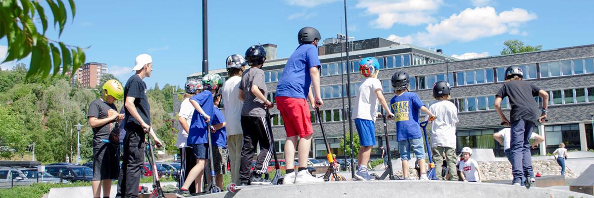 Barn och ungdomar åker kickbike på skatepark
